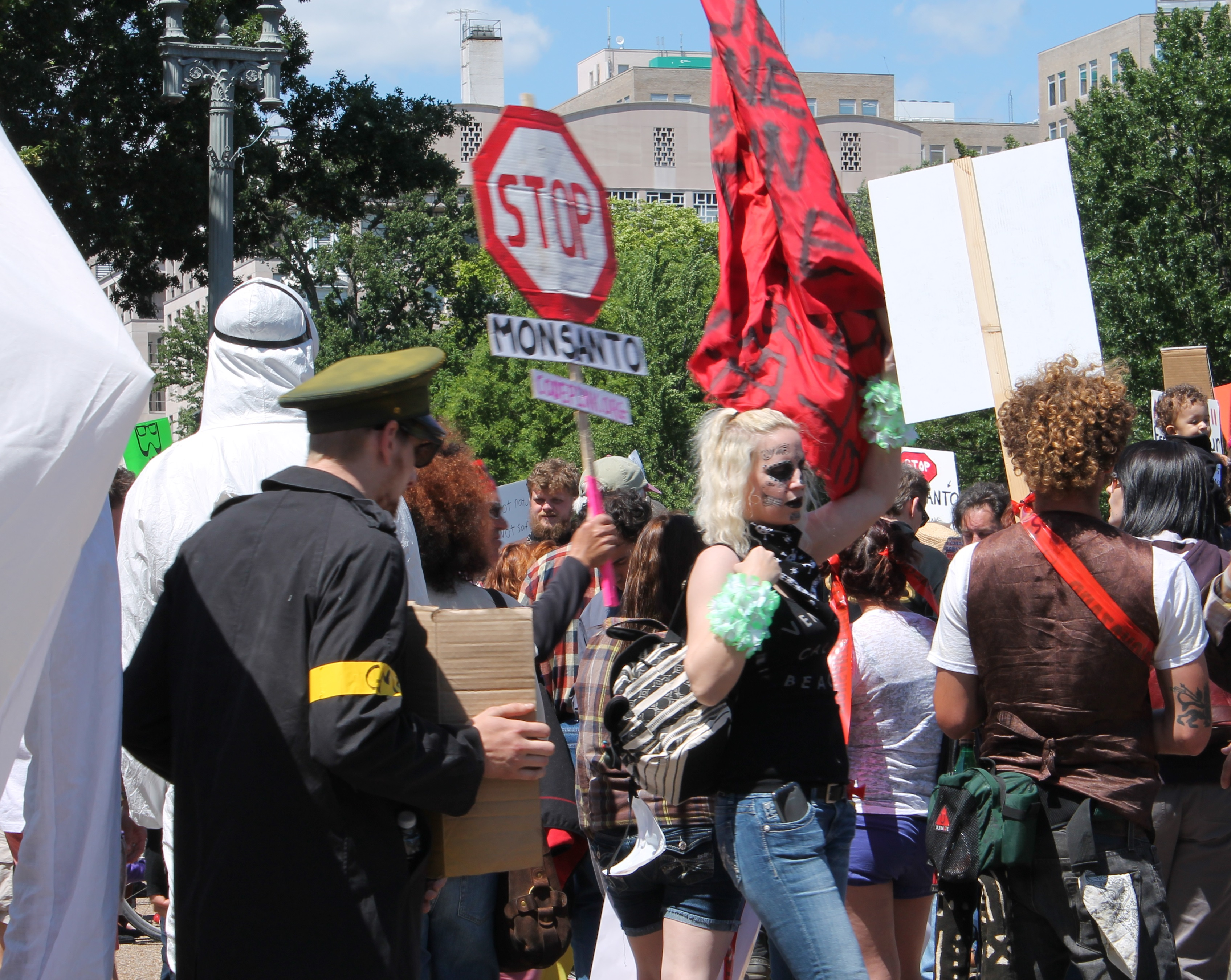 """A group of protesters. One holds a stop sign that says """"Stop Monsanto""""."""